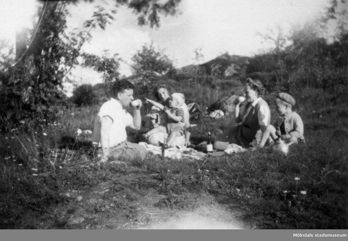 Familjerna Garthman och Eriksson sitter i det gröna och fikar i Mölndal. Från vänster: Helmer Garthman, Doris Eriksson med Bert Eriksson i knät, Astrid och Alf Garthman. 1950-tal.