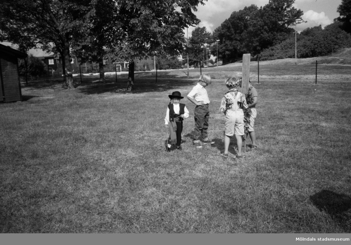 Fyra barn från Katrinebergs daghem står utomhus på en stor  inhägnad gräsmatta. Ett litet barn, iklädd hatt, väst och käpp, går mot fotografen. Ett par av barnen håller en stående träplanka. I bakgrunden ser man några hus samt höga träd.