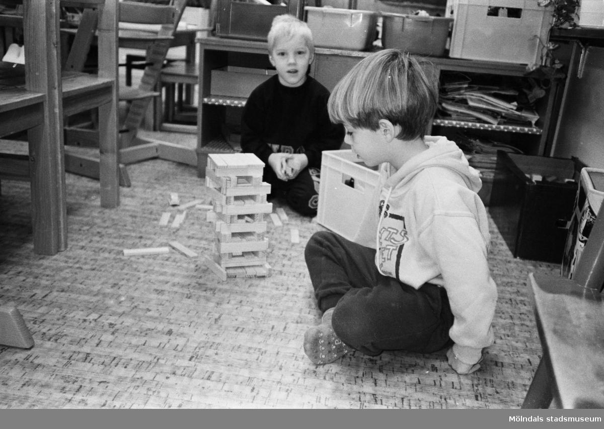 Två pojkar, vid Katrinebergs daghem, sitter inomhus på golvet och sätter ihop en byggsats av avlånga träbitar i miniformat. Hittills är modellen ca 20 cm - men vem vet hur hög den kan bli...