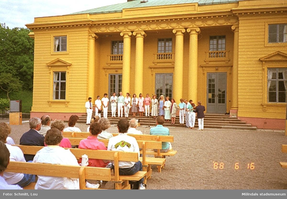 En sångkör samt två fiolspelande män står uppställda på trappan till det gulmålade Gunnebo slotts framsida. På grusplanen framför sitter publik i bänkar och lyssnar.