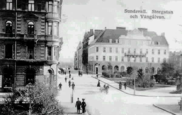 """Från vänster kv Olympen 4/ Kihlmanska huset, Storgatan och till höger kv Proserpina 1/Sundsvalls handelsbank, Sunessons Bokhandel och i höger förgrund parken Vängåvan. På Storgatan fotgängare samt en häst och vagn. Text  till bild """"SUNDSVALL. STORGATAN och VÄNGÅVAN."""""""