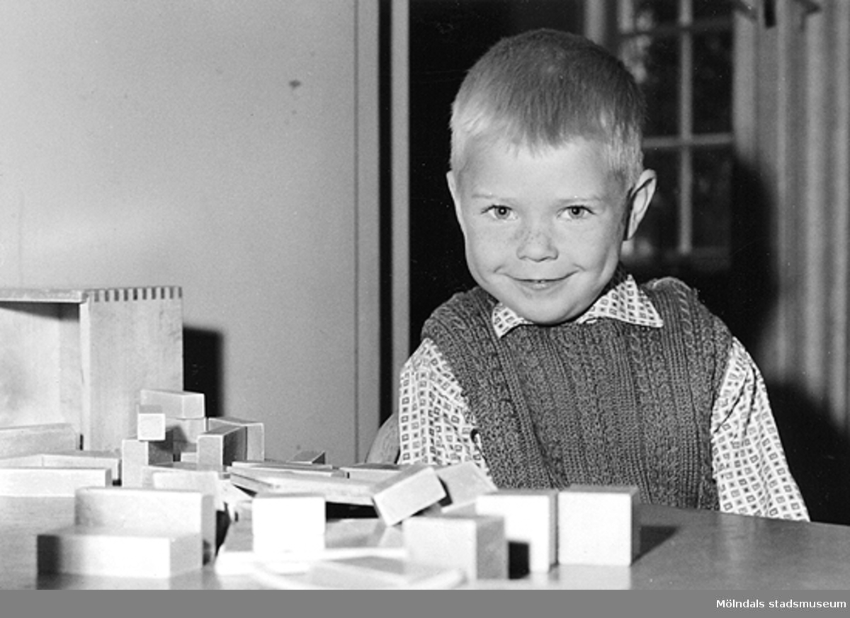 En leende pojke som leker med klossar. Holtermanska daghemmet 1953.