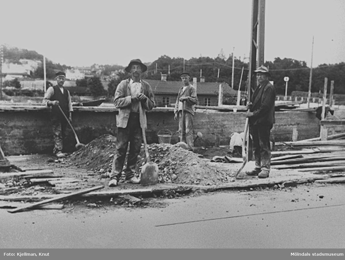 Fyra män poserar med spadar i händerna. De är med vid anläggningen av Spårvagnshallarna som låg i hörnet mellan Kvarnbygatan och Göteborgsvägen.