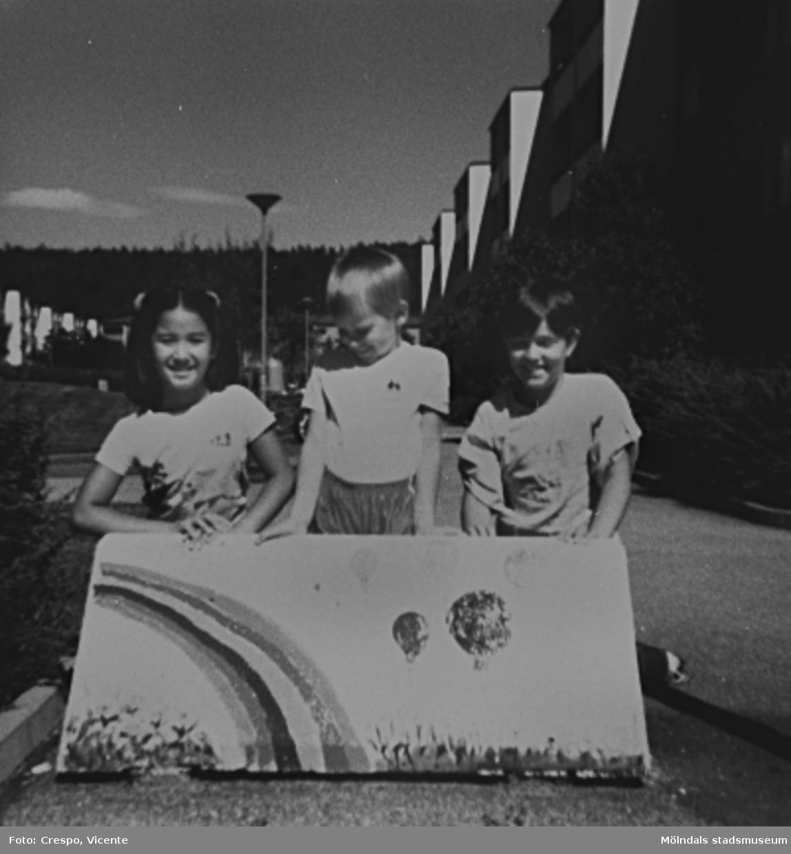 """De tre barnen Dos-Alva, Helena och Carita, boende i bostadsrättsföreningen Tegen, som målade """"suggorna"""" (väghindren) på föreningens område i början av 1980-talet. Barnen är namngivna från vänster."""