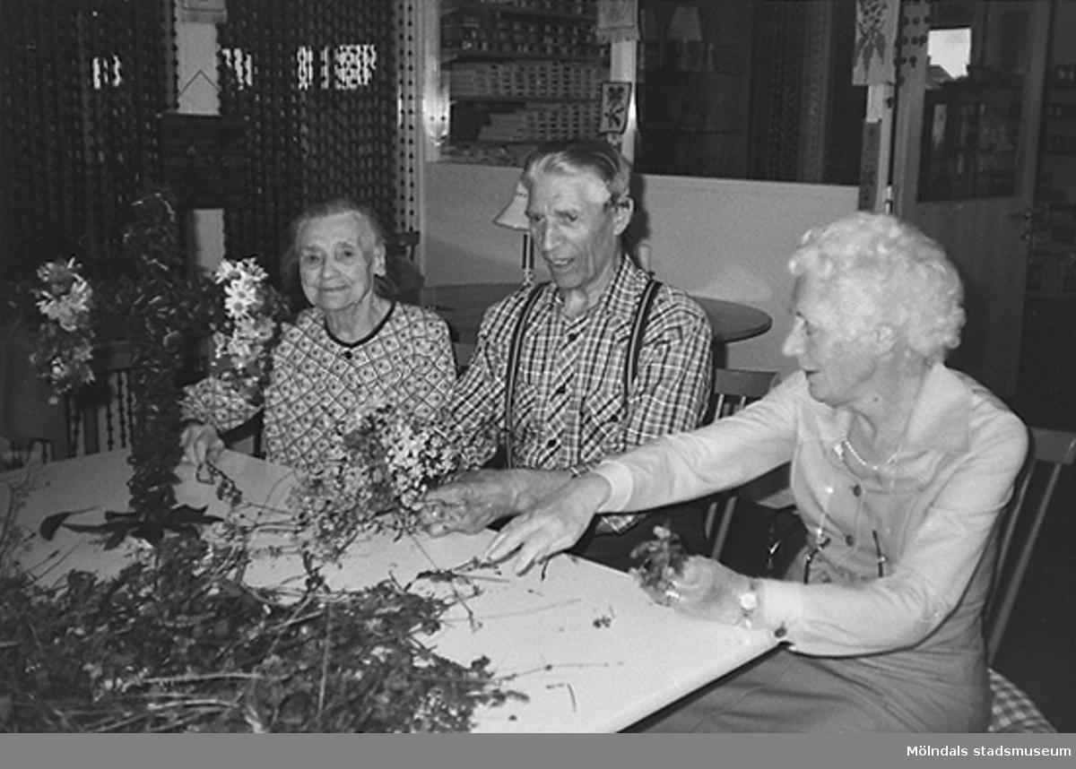 Två kvinnor och en man plockar bland blommor. De klär en liten midsommarstång som står på bordet framför dem. Okänt årtal.