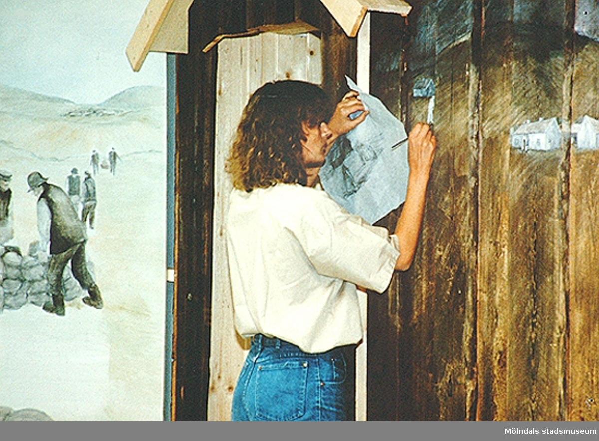 En okänd person målar en vägg vid uppbyggnad av Mölndals museums basutställningar.
