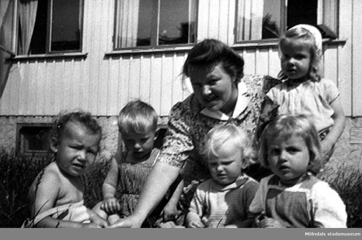 """Håkan Carlsson och andra barn med en lärare på Krokslätts daghem, Dalhemsgatan 7 i Krokslätt. Under Margit Emilssons (gift Wannerberg -52) praktik som biträde1945-10-01 - 1946-08-01.""""Håkans charm och hans rara föräldrar bidrog till att jag valde yrket, barnträdgårdslärarinna. Jag var otröstlig när jag skildes från Håkan - då jag slutade för att börja på seminariet.""""   Enligt Margit Wannerberg."""