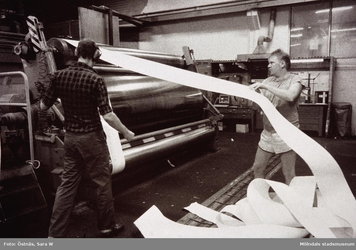 Två män i arbete vid banbrott på Papyrus i Mölndal, år 1990. Mannen som drar i remsen är Kent-Erik Pettersson.