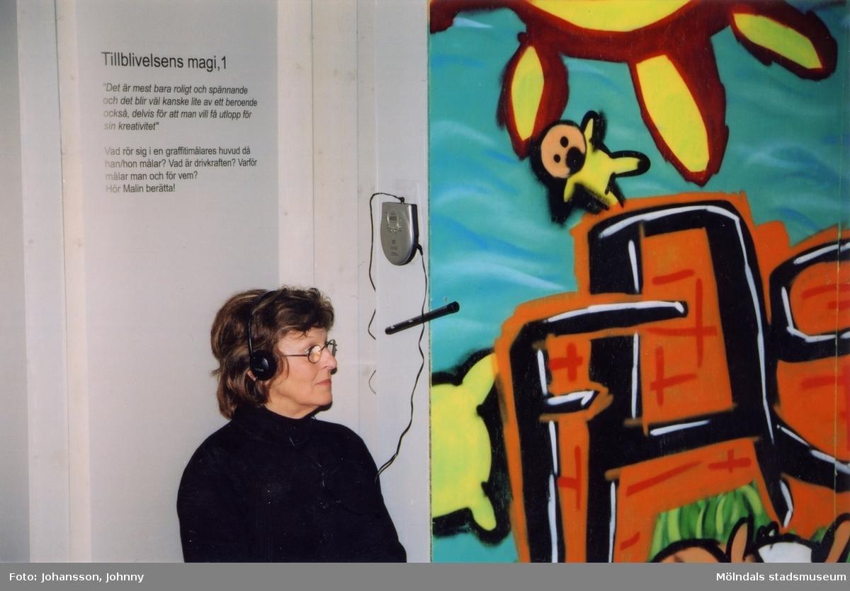 """Kvinna med hörlurar i utställningen """"Alltså finns jag"""" på Mölndals museum, år 2003.  Utställningen """"Alltså finns jag"""" ...en utställning om graffitikultur på Mölndals Museum, Kvarnbygatan 12, Mölndal, pågick från 25 januari till 25 maj 2003. """"Alltså finns jag"""" var ett samarbete mellan Mölndals museum, Vitlycke museum, Bohusläns museum, Västergötlands museum och Konstkonsulenterna i Västra Götalandsregionen."""