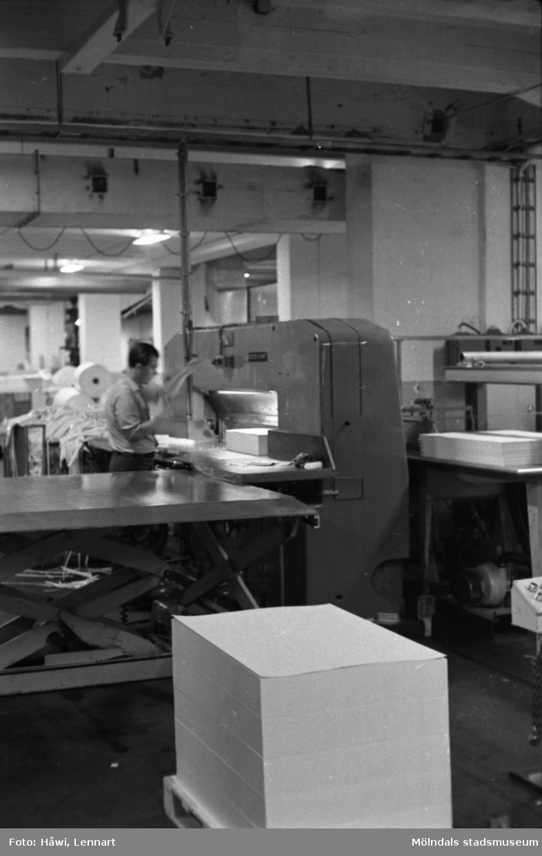 Man i arbete vid skärmaskin på Papyrus i Mölndal, hösten 1970. En pall med papper som kommer från klippen. Skärsalen, tredje våningen? Byggnad 18.