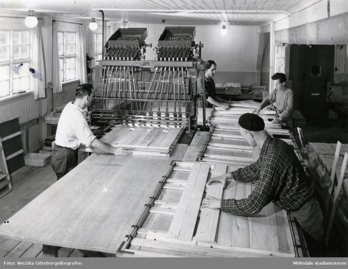 """Fyra män i arbete vid ramverkstaden på Papyrus. Arbetet sker med hjälp av spikmaskin.Birger Andersson (1909-2004) arbetade på Papyrus mellan 1924-1976. Hans arbetsplats var ramverkstaden där de spikade lastpallar och """"bottnar"""", som användes för att skydda pappret vid packningen med stålband. Under sina 52 år i ramverksta'n spikades bottnarna för hand i ca 30 år. Resterande tid med hjälp av spikmaskin. Birger Andersson var spikare."""