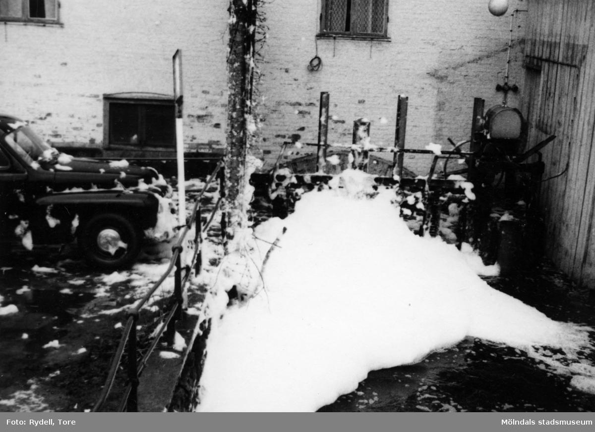 Soab har släppt ut kemikalier i forsen vilket har resulterat i skum.Fotografi ur album som tillhört Christina Rydell. Bilderna i albumen är delvis från Papyrus där Christinas far Tore Rydell arbetade, men också från Kvarnbyn, Ryet och folkliv i Mölndal. Tore tog ofta med sig kameran till Papyrus där han fotograferade sina arbetskamrater i arbete, men också fester och föreningsliv.