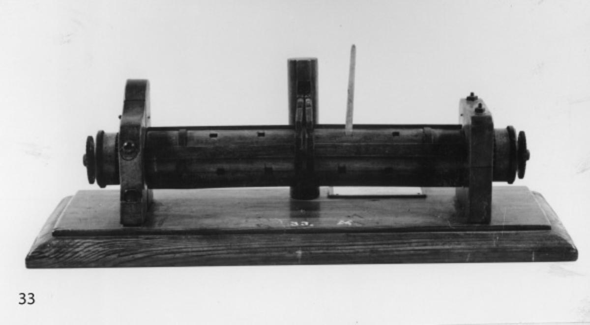 Modell av engelskt bråspel, av trä, fernissad, med beslag av järn, fastsatt på en träplatta motsvarande ett däck samt med pallarna fästade till en pallbeting som skulle kunna vara en mast. Utrustad med två sekundära spelspakar. Modell av fernissat trä.