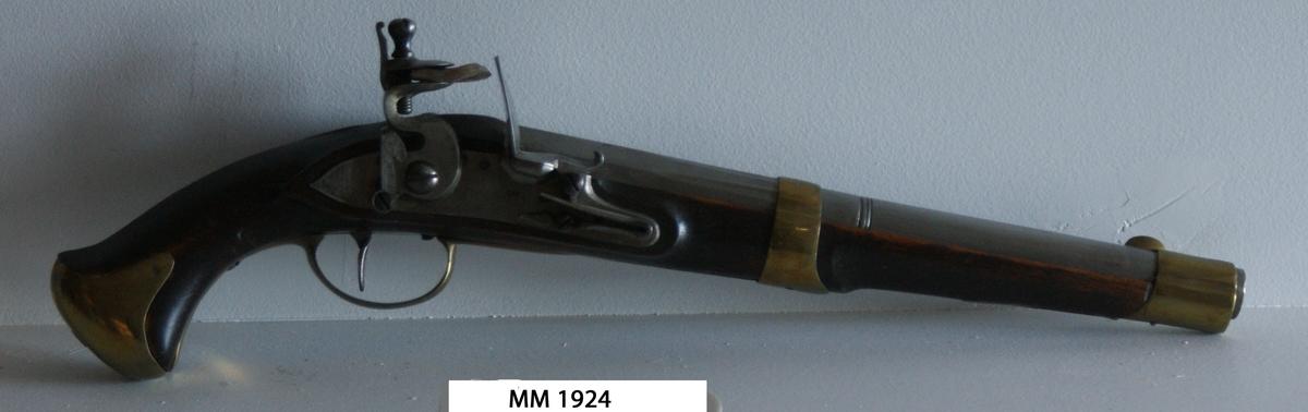Pistol med flintlås, troligen förändringsmodell av år 1807 eller 1808. Stocken av trä, brun. Pipa och mekanism av stål. Beslagen av mässing. Kammarstycket 5-kantigt, märkt AH med krona över och därunder H och NT. På sidan GN.
