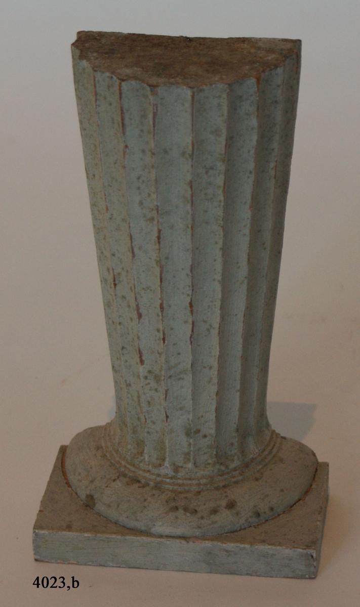 """Pelare, eller kolonner, släta och räfflade (7 st halvkolonner, räfflade). 20 st. modeller av trä, avsedda som fasadprydnader. Pelarna är räfflade med halvcirkelformig basyta. De är vitmålade. Kapitälen är av närmast dorisk stil. Pelarna utgör modeller till gavelkonstruktion för nya inventariekammaren på varvet 1785-87. De sammanhängs troligen med en serie av gavelmodeller och pelare, som finns i kistan i sal 1 och vid norra delen av väggen i samma sal. (K 2244)  Halvkolonn, kannelerad med kapitäl och fast abakus. Målad i gråvitt. Tidigare märkt: """"8"""" """"2244""""."""