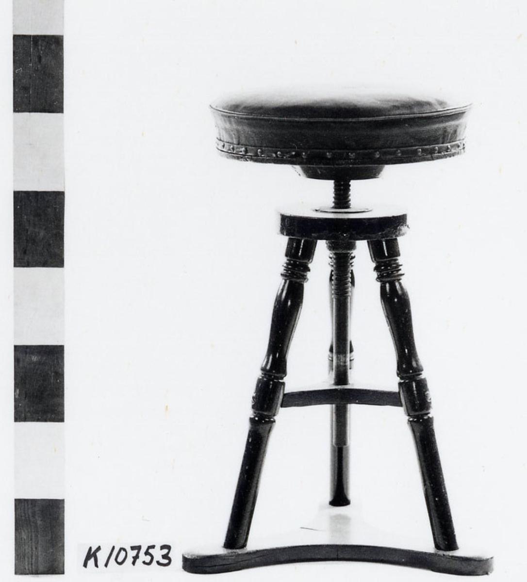 Skrivbordsstol av mahogny, även kallad skruvstol (pall). Rund sits, stoppad och klädd med skinn. Tre svarvade ben stående på triangulär fot. Skruv för höjning och sänkning av sitsen.