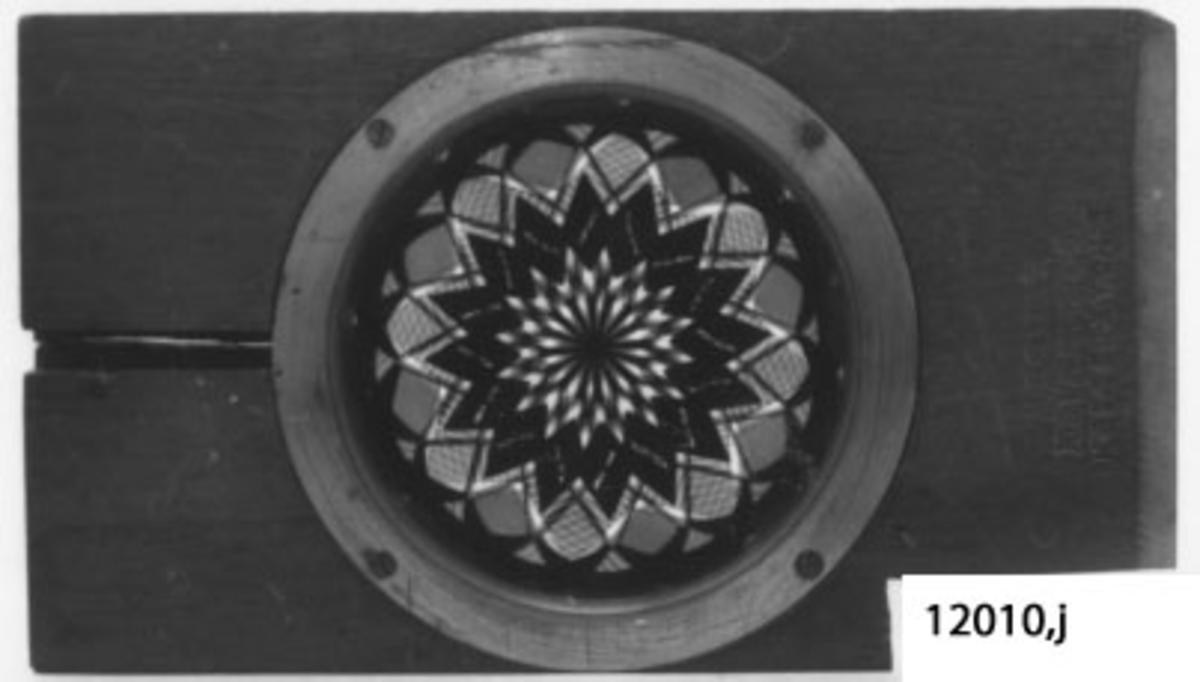 Rektangulär träram med cirkelrund infattad glasskiva med motiv: stjärnmönster. Plattan märkt: D. NOAKES & SON, GREENWICH, LONDON