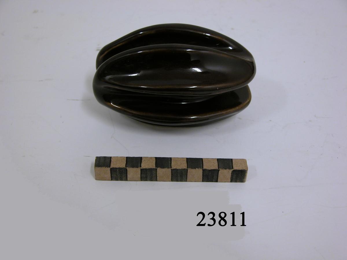 Isolator av porslin, brun glasyr. Äggformad med två djupa spår för ledning.