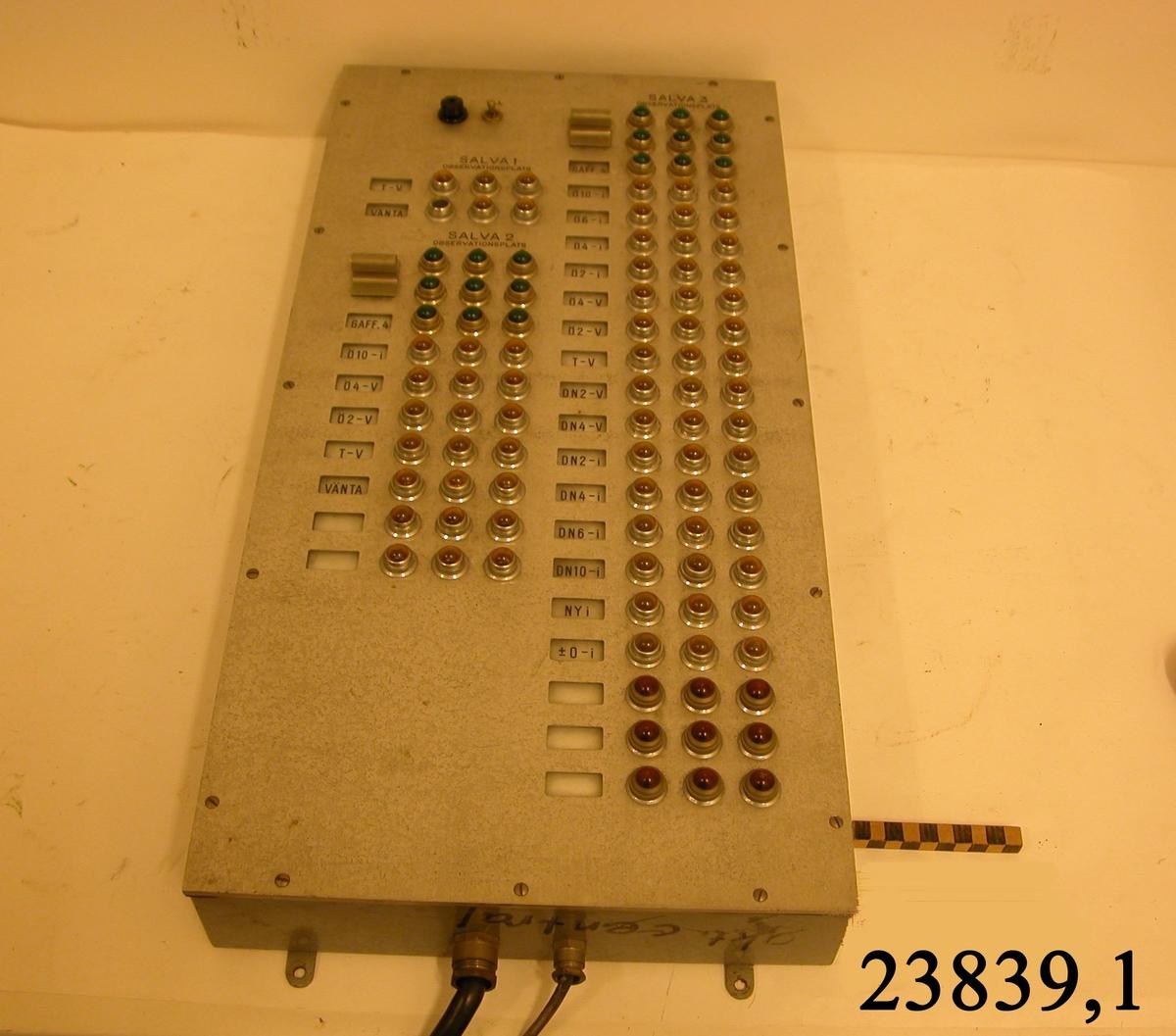 """Rektangulär låda av metall med rader av kontrollampor av gul och grön plast. Vid sidan av lampraderana, små fönster som visar olika siffer och bokstavs kombinationer för """" SALVA 1, Observationsplatser 1,2,3. SALVA 2, Observationsplatser 1,2,3 och SALVA 3, Observationsplatser 1,2,3, Överst en knapp """" TILL """""""