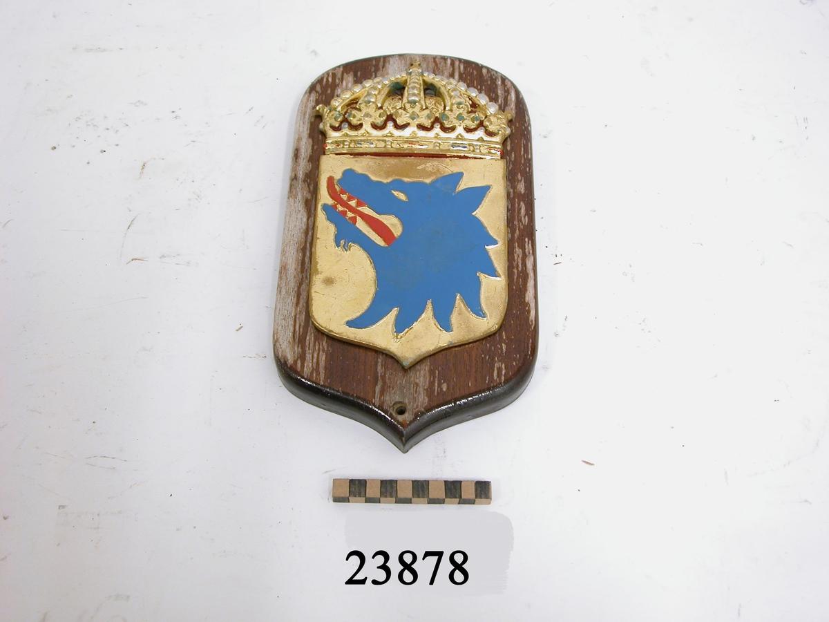"""Vapensköld gjuten av mässing, krönt med kunglig krona, målad i heraldiska färger (färgerna skavda samt ärgbelagda). Botten i guld, därpå ett avslitet blått varghuvud med röd tunga och röda tänder. Skölden är fästad vid fernissad platta av trä. Symboltolkning: """"Vidar- som var son till Oden- dräpte underjordens odjur Fenrisulven, vars huvud utgör vapensymbol"""". Källa: Stadsheraldiker Jan von Konow."""