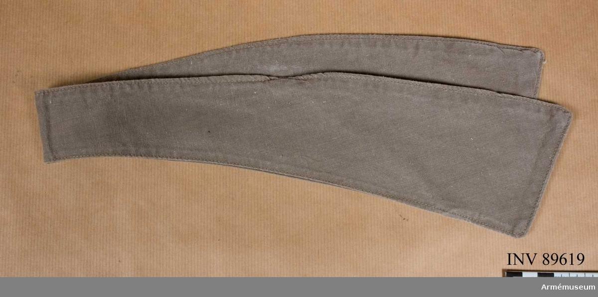 Sydd av gråbrungrönt bomullstyg, svängd och smalare mitt bak. På avigsidan en slå av tyget fastsydd på skrådden varigenom den motsvarande slipsänden träs.