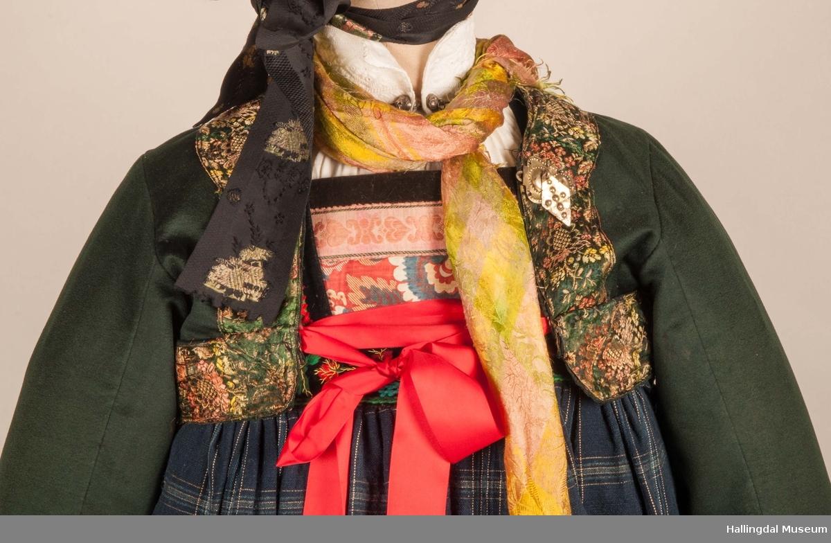 Kone fra Nedre Hallingdal i hallingbunad.  Kona står utstilt i den faste bunadutstillingen på Hallingdal Museum, Nesbyen.  Hallingbunaden består av mange draktdeler; trøya HFN 01835, Forkle HFN 03381, stakk, liv, lue, silketørkle rundt lua, silketørkle rundt halsen HFN 03500, bringduk og skjorte.