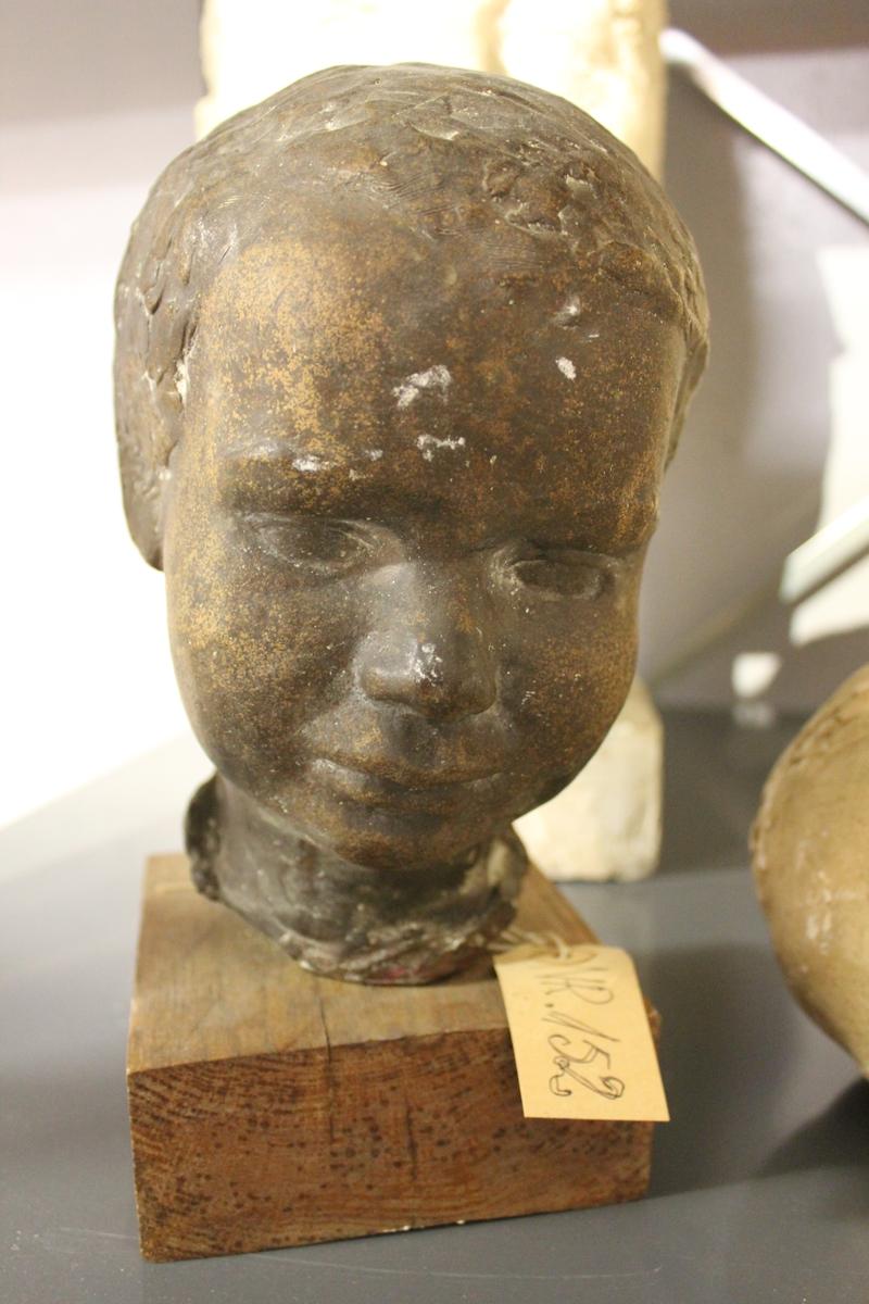 Portretthode i bronse av et barn på sokkel i tre. Samme som nr.151