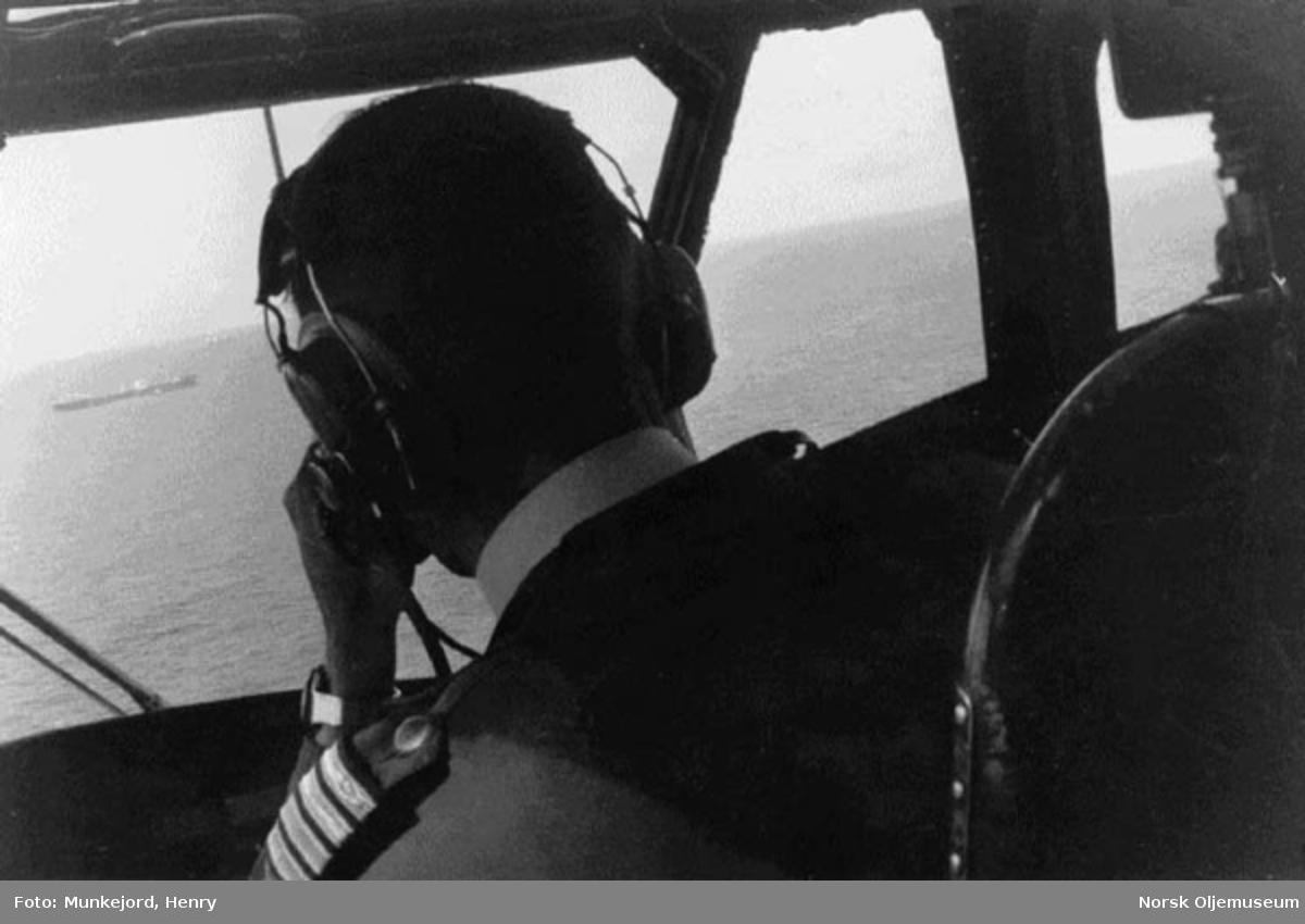 Helikopterpilot fører et helikopter ut til Ekofisk-området.   Tankbåt synes i horisonten.