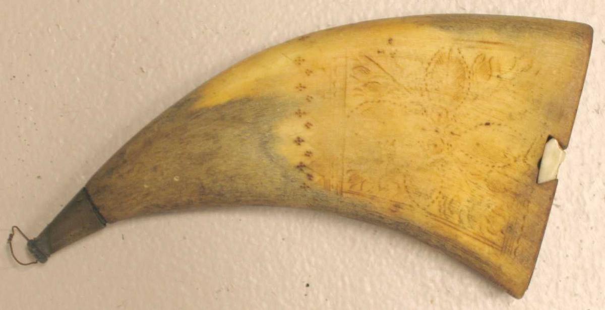 Form: Av kuhorn, flatpressa og pynta med innbrente blomsterteikningar. Messingbeslag på enden med ein tretapp i den. Trebotn med skyveslå av bein.