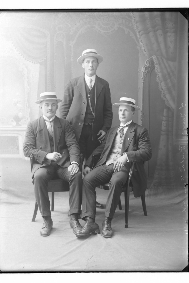 Studioportrett av tre menn med stråhatter.