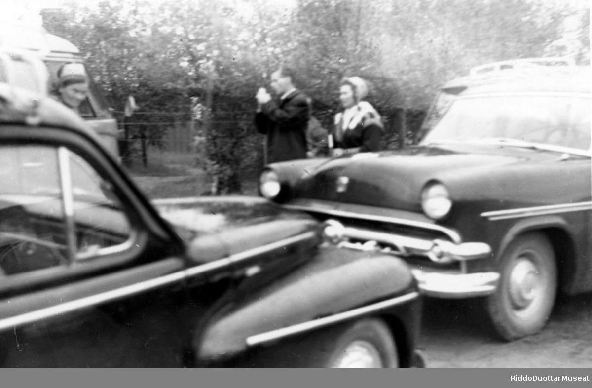Nissonolbmot ja dievdoolmmoš cužžot guovtti biilla duohken. Kvinner og en mann står bak to biler.  Volvo PV444, Ford Customline.