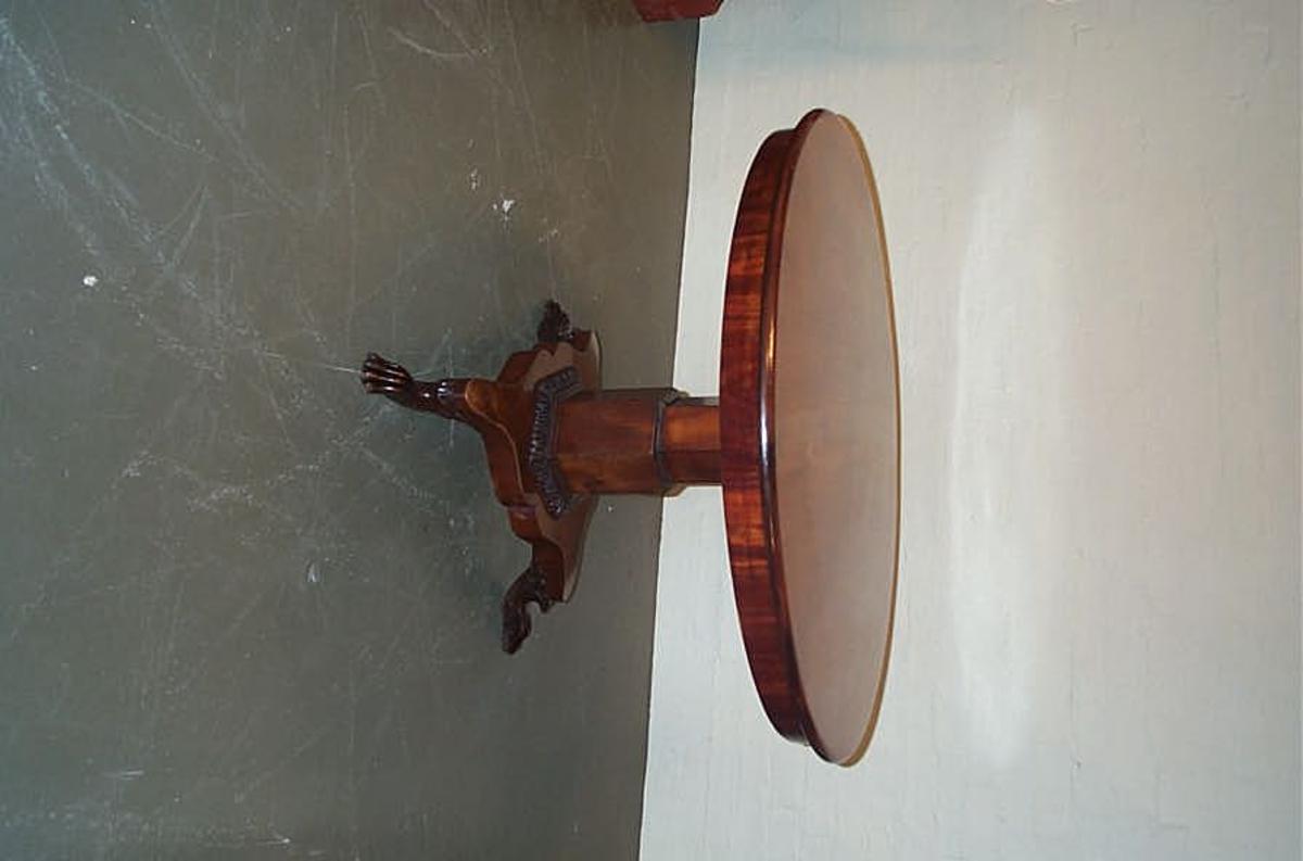 Form: Sirkulært tversnitt. 6-kanta fot, plassert sentrert under bordplata, festa til 3-kanta profilert fotplate på 3 løvebein. Utskjeringar på over- gangsstykkjet/delen mellom fot og fotplate. Datering 1890-1910 ca.