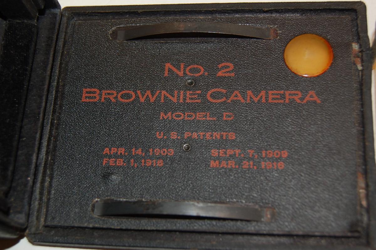 Kamera i mørk brun boks, lerinnbunden boks av papp.Handtak i topp. Kan opnast i bakenden. 2 namnplater i metall bak, ein frå fabrikk og ein frå forhandlar. Enkel linjedekor innprega i skinnet.