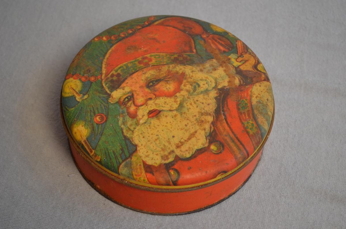 Rund kakeboks. Raud med julemotiv. På loket er det avbilda ein nisse med eit juletre i bakgrunnen. Ein del rust.