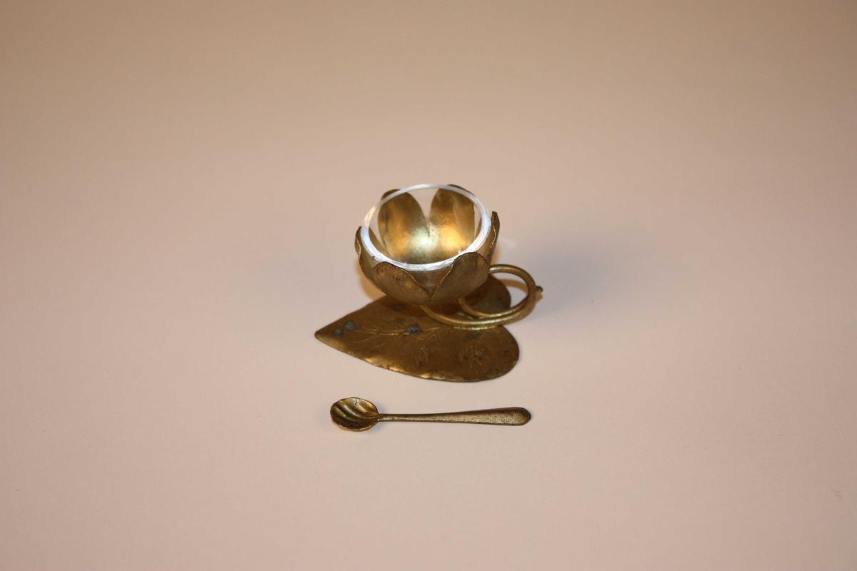 Saltkar med haldar forma som ei vasslilje eller lotusblomst. Oppi kronblada står ei glasskål til saltet. Ei lita skei høyrer til. Haldaren er måla av eigarane, sjå SUM.05013 bronsetinktur og SUM.05017 bronsemaling frå same gjevar.