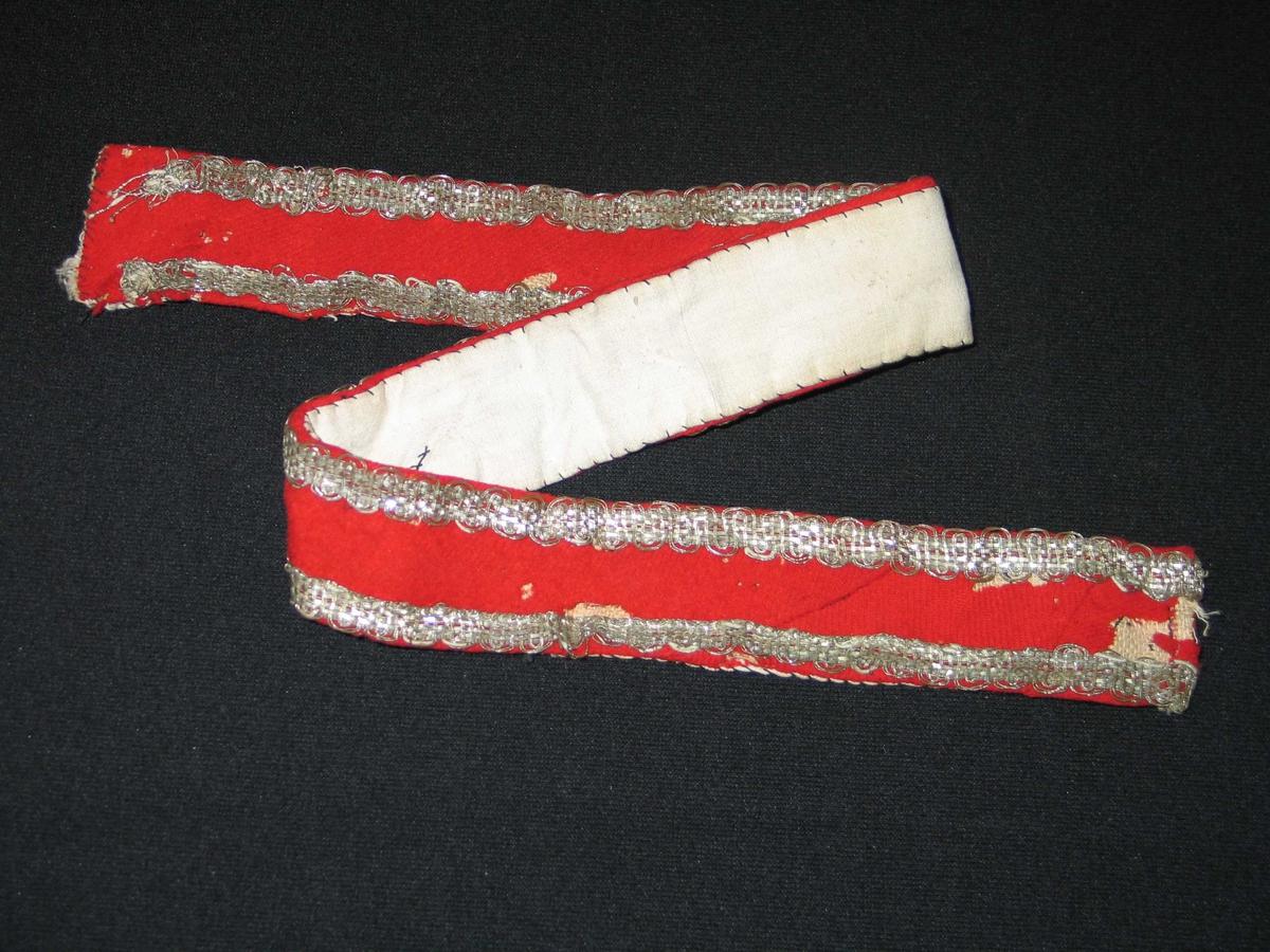 Raudt ullstoff på strie med to kantband i fletta metallband