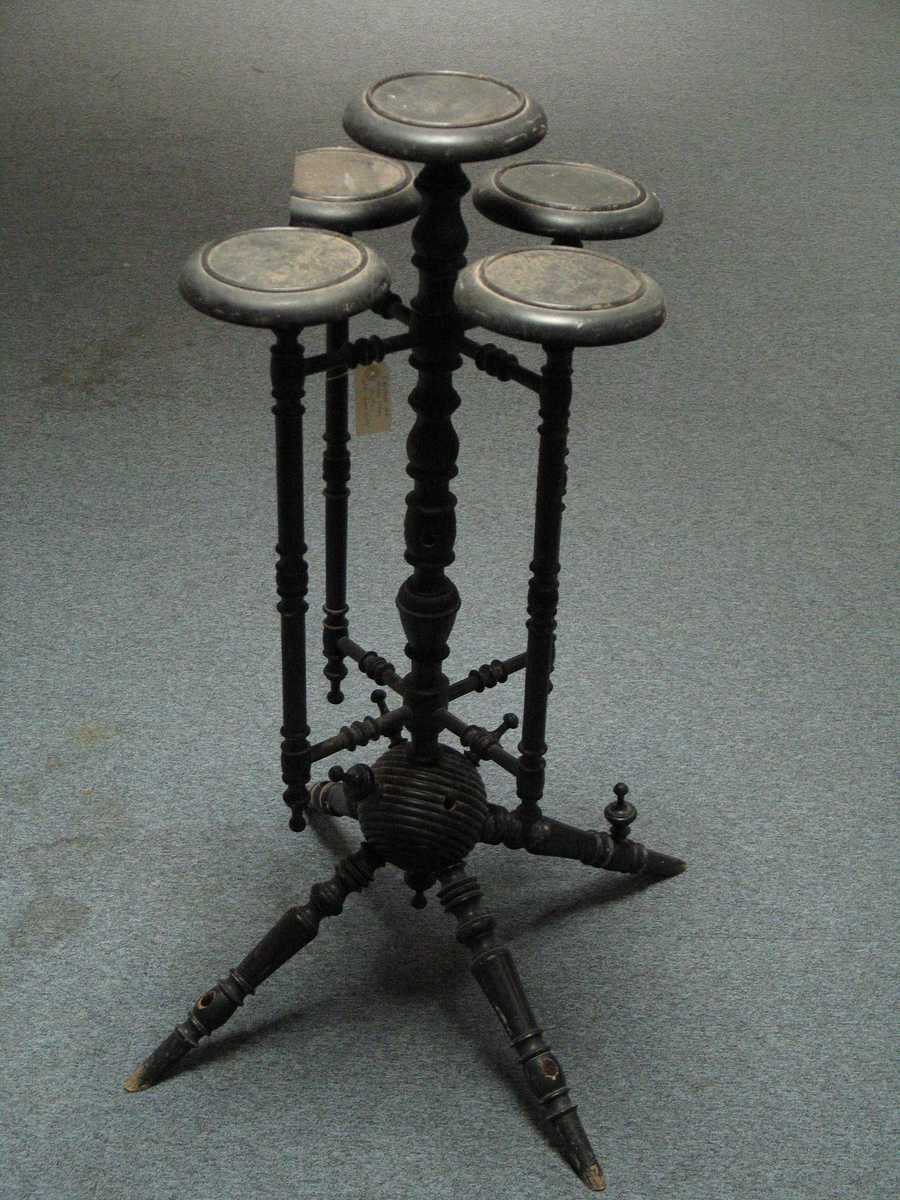 Pidestall med fem bord - eit i midten og 4 rundt. Sett saman av mange dreia deler. Det har vore nytta som atelierdekorasjon hjå Olai Fauske