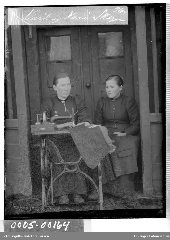 Portrett av to kvinner ved en symaskin foran en inngangsdør.