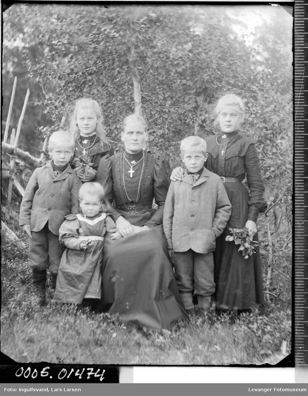 Gruppebilde av en kvinne og fem barn.