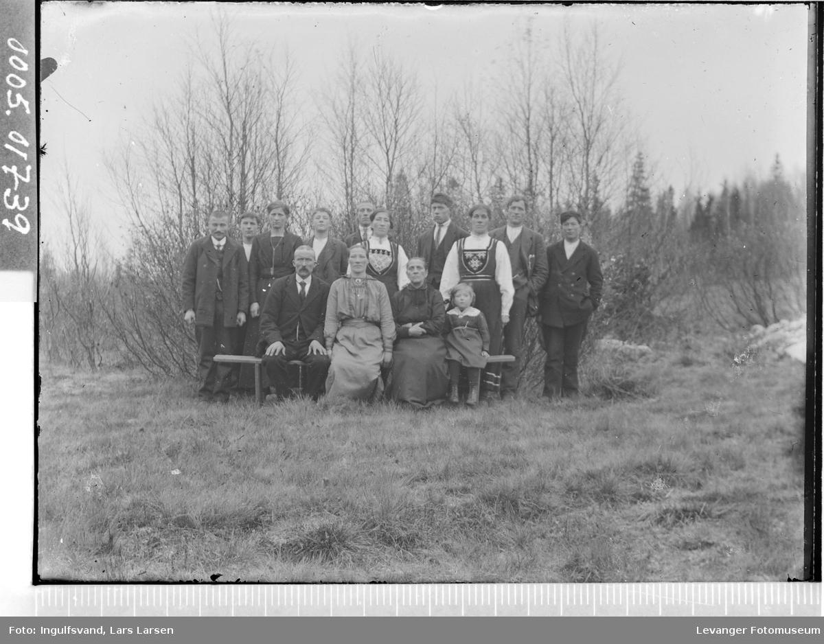 Gruppebilde av syv menn, seks kvinner og et barn.