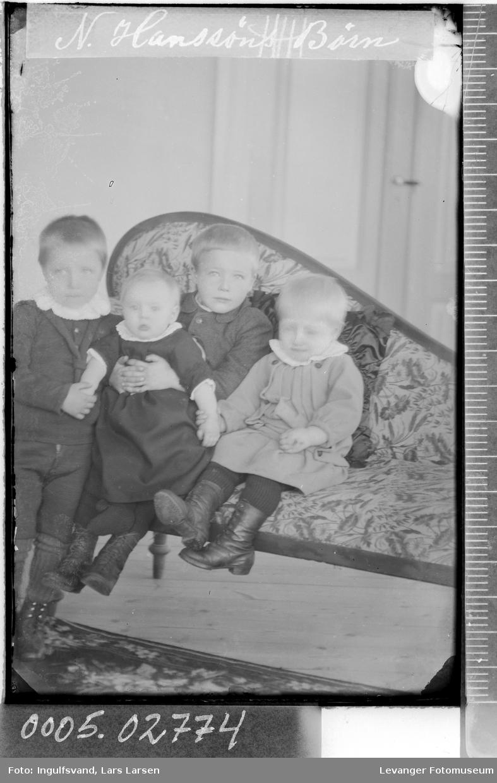 Gruppebilde av fire barn på en sofa.