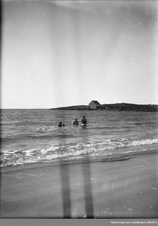 Tre kvinner med badehette og badedrakt bader like utenfor en strand (bare hode og skuldre stikker opp av vannet). Muligens samme sted og tidspunkt som ST.K.HE 2007-011-0056 til -0058.
