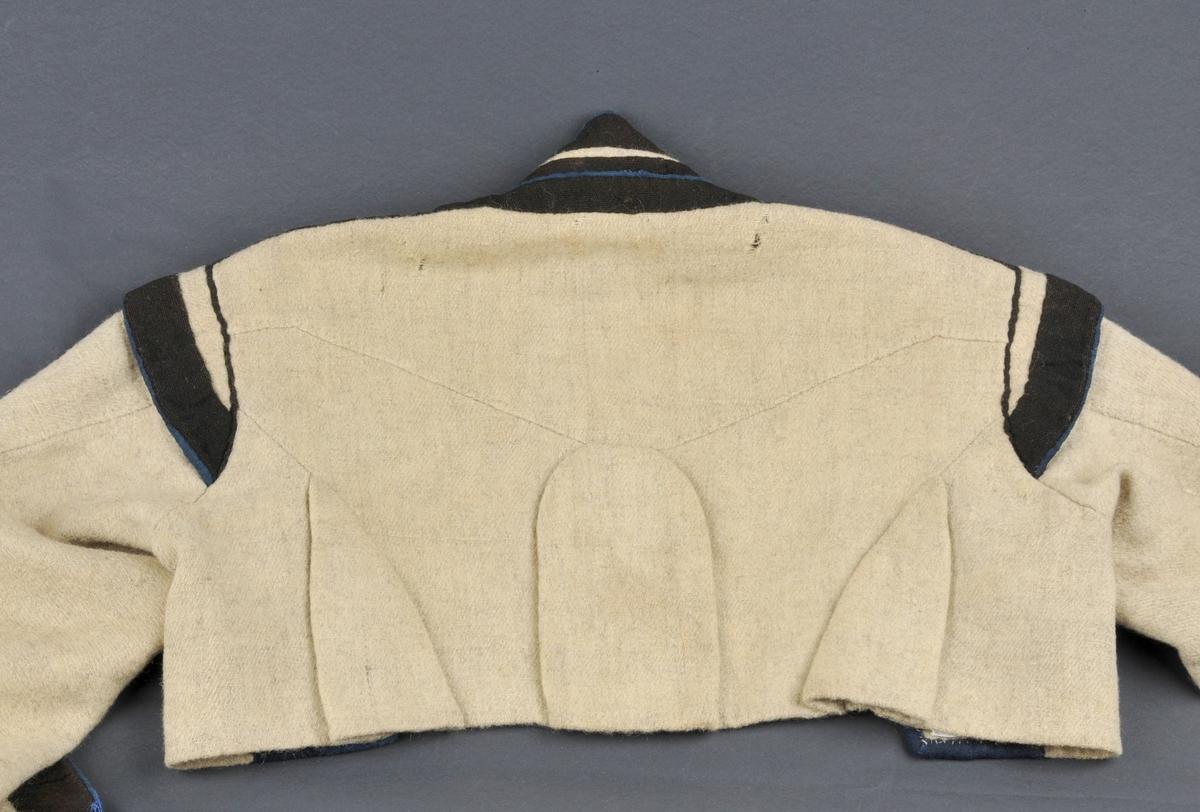Gråkvit vadmål. Armane er kanta med 3.5 cm svart ullverken. Ytterst ein 3 mm smal synleg blå kant av ullverken. Splitt 8.5 cm. På akslene 3.0 cm brei svart og 3 mm blå kant. Ved akslesaumen og på framsida svarte belegg med den same blå markeringa. I ryggen 3 legg. Legg i sidesaumane bak. På vranga midt på ryggen nede er det sydd eit merke med blå ulltråd som kan vere ein J eller E.