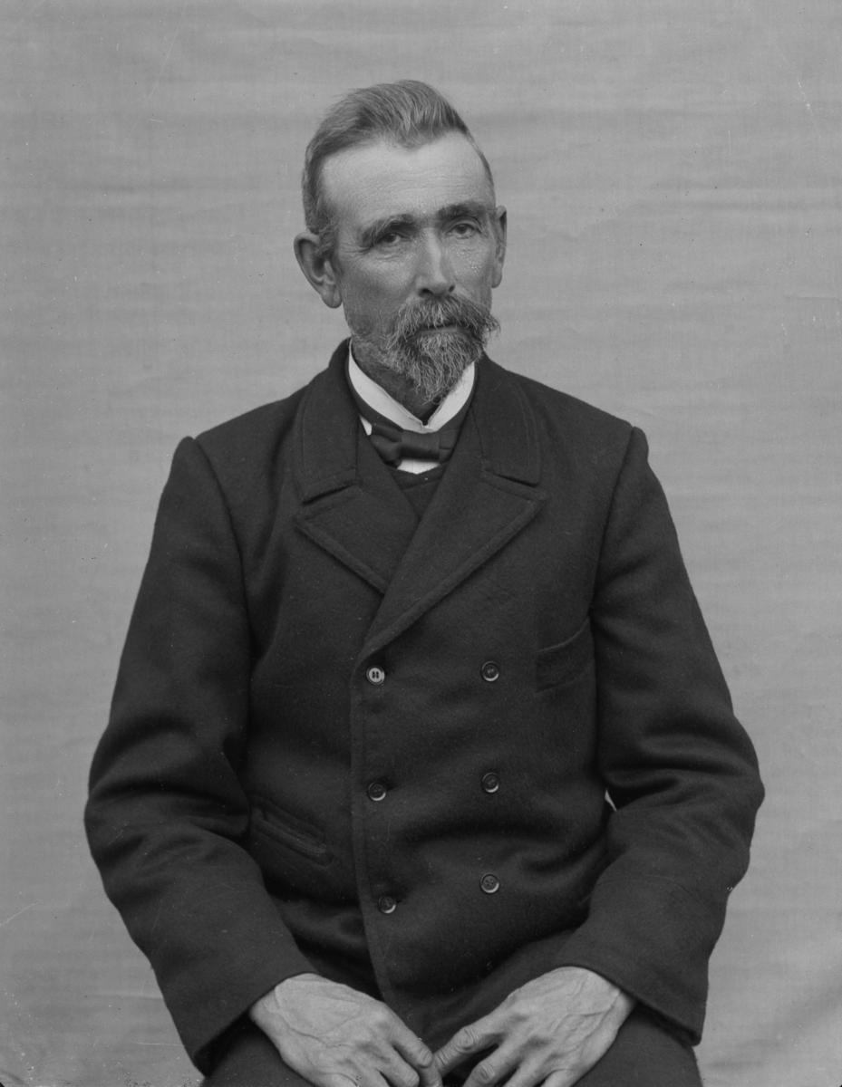 Dresskledd mann sittende foran hvitt lerret