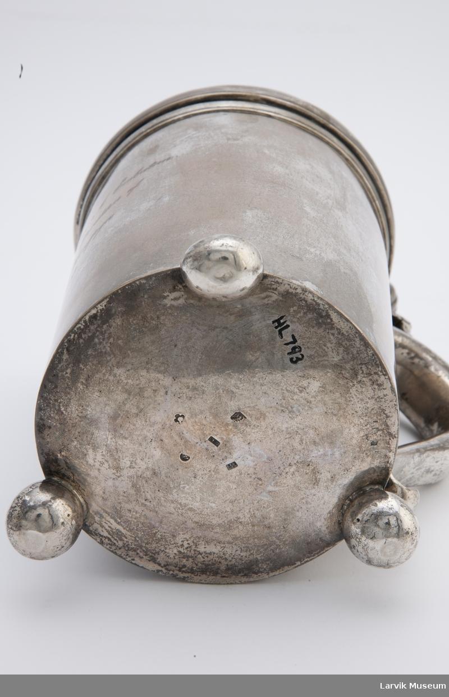 Form: avr. lokk festet til håndtak. Kruset står på tre kuler/ben som er festet til bunnen