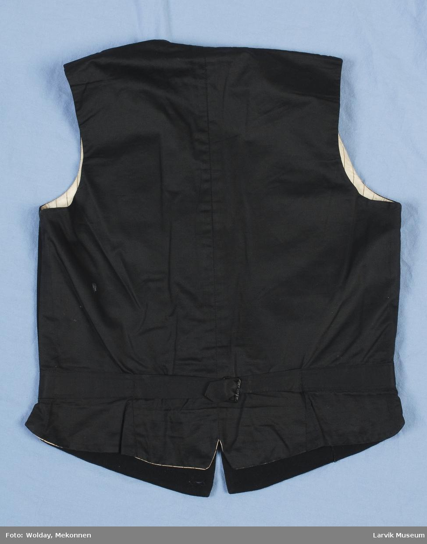 Form: Vest med buet krage, fire knapper tre lommer. Spenne med bånd til å stramme bak.