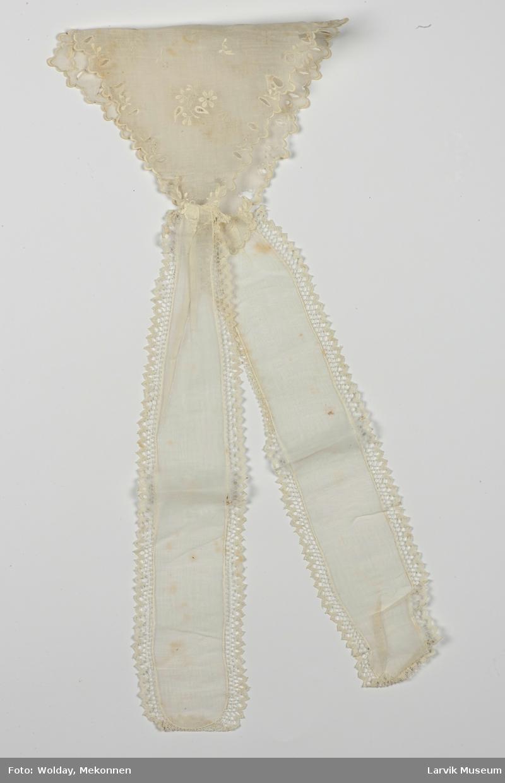 Form: To avrundede bånd som er sydd fast til et stykke i ruterform. Hullbroderi langs kanten, og på midten. Blonde på bånd.
