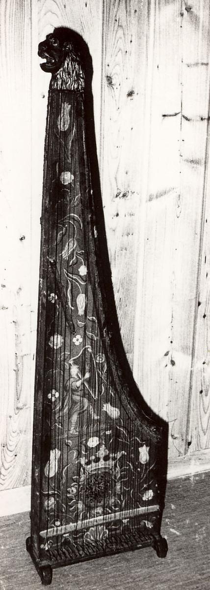 Toppstykket form av et utskåret løvehode. Malt dekorasjon ( blomster, fugl, harpespiller)