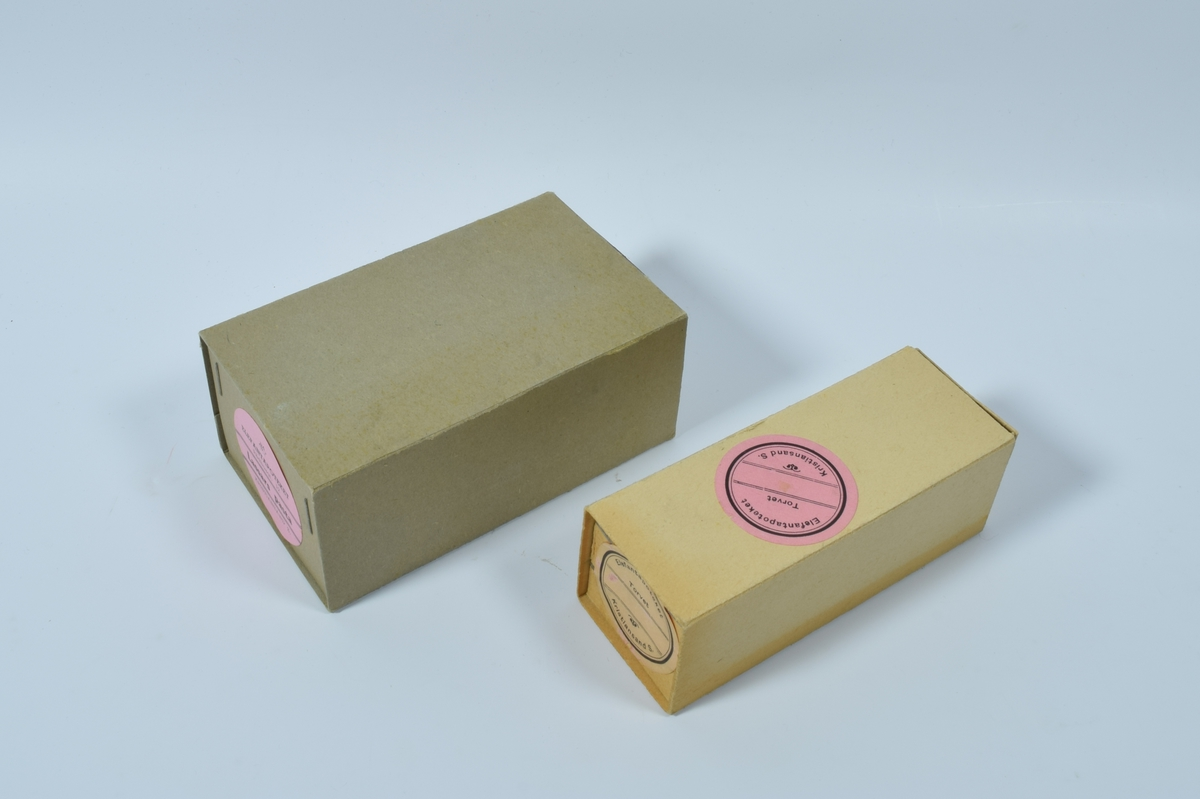 """Ni rektangulære esker i papp med runde, rosa etiketter fra Elefantapoteket med sort skrift. Et eksemplar av etikettene er limt på en av kortsidene på hver eske. Alle etikkene, untatt etikettene i eske a, har en bord i form av en tykk og en tynn sirkel.   Eskene består av to separate deler, hvor den ene ligger inne i den andre og kan skyves ut. Alle de innerste eskene, untatt eske b, er stiftet sammen i hjørnene.  Eske a er i brun papp med etiketter for """"Lassars pasta"""".  Eske b er i rød papp med etiketter for """"Svovlvaselin"""".  Eske c er i lysebrun papp med lyserosa etiketter og et blankt felt  Eske d er i hvit papp med etiketter for """"Zinksalve"""".  Eske e er i brun papp med lyserosa etiketter for """"Gul Sårsalve"""".  Eske f og g er  i hvit papp med etiketter for """"Mentholvaselin"""".  Eske h er i lyserosa papp med etiketter for """"Kamfersalve"""". Esken og etiketten på kortsiden er svært slitt.  Esken er forsøkt teipet sammen.  Eske i er i rosa papp med etiketter for Svovelvaselin. Esken og etiketten på kortsiden er svært medtatt. Esken er forsøkt teipet sammen."""