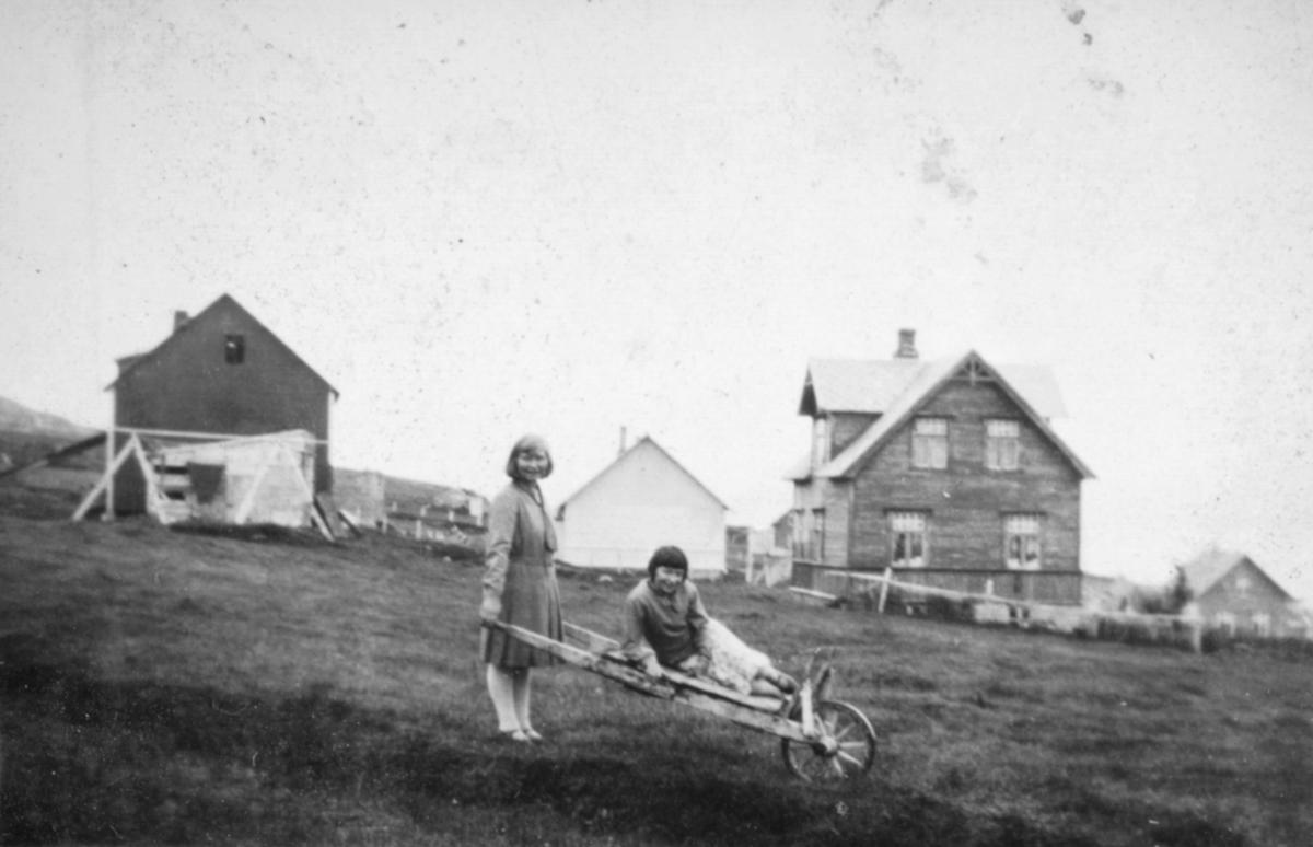 To kvinner ute på en gårdsplass foran noen hus og bygninger. Sted og personer er ukjent, men bildet kan være tatt i Kvalsund kommune.